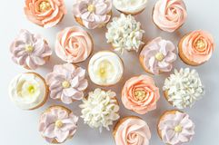 Mini cupcakes decorated with buttercream flowers. Top-down view of pastel colored mini cupcakes decorated with buttercream flowers royalty free stock photos