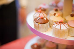 Mini cupcakes on a multi level tier. Pink and brown Royalty Free Stock Photos
