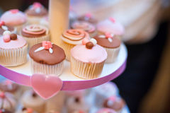 Mini cupcakes on a multi level tier. Pink and brown Royalty Free Stock Images