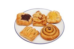 Mini Danish pastries. On a plate isolated against white Royalty Free Stock Image
