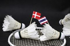 Mini Denmark flag and mini Thai flag stick on the shuttlecock put on the net of badminton racket and other shuttlecocks around it. On the black floor. Concept royalty free stock photos