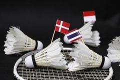 Mini Denmark flag and mini Thai flag stick on the shuttlecock put on the net of badminton racket and out focus Indonesia flag. And shuttlecocks around it stock photos