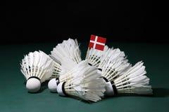 Mini Denmark flag stick on the heap of used shuttlecocks on green floor of Badminton court. With dark black background stock photography