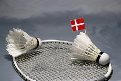 Mini Denmark flag stick on the shuttlecock put on the net of badminton racket and a shuttlecock. On the grey floor royalty free stock photos