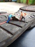 Mini- diagram leksakarbetarkäk upp grus från svart rubber halt royaltyfria bilder