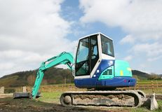 Mini Digger. Standing idle on rough ground in rural countryside stock images