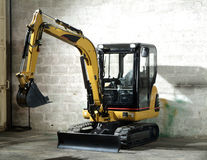Mini digger. Parked in the mechanic garage Stock Image