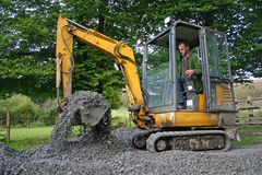 Mini digger. Small digger moving sub base royalty free stock images