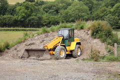 Mini Digger. With excavator bucket standing idle on rough ground, with countryside to the rear Stock Images