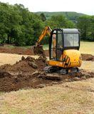 Mini Digger. Man operating a mini digger in a field stock photo
