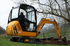 Mini Digger. Man in a mini digger digging a trench in a field stock images