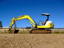 Mini Digger Excavator. A yellow and white mini digger excavator. Space for Copy stock photography