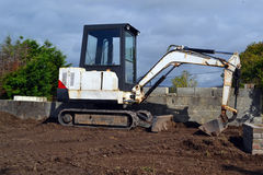 Mini digger. Small mini digger on a residential building site stock photos