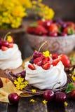 Mini dolce delizioso della meringa di Pavlova decorato con berrie fresco immagine stock