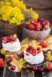 Mini dolce delizioso della meringa di Pavlova decorato con berrie fresco fotografia stock