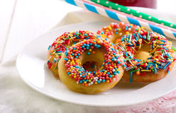Mini donuts with sweet sprinkles. On plate Stock Photos