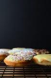 Mini Doughnut Cakes adornado en el estante de enfriamiento con Backgro negro Fotos de archivo libres de regalías