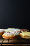 Mini Doughnut Cakes décoré sur le support de refroidissement avec Backgro noir Photos libres de droits
