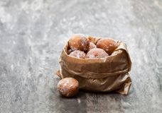 Mini  doughnuts in paper  bag on rustic wooden table Stock Photo