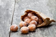Mini  doughnuts in paper bag on  rustic wooden table Stock Images
