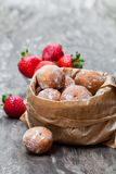 Mini  doughnuts stuffed with  strawberry jam in paper bag on rust Stock Images