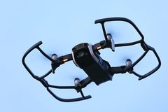 Mini drone floating in blue the sky to record videos and take pictures Royalty Free Stock Images