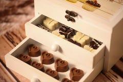 Mini dulces del chocolate en una caja de madera Foto de archivo