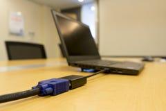 Mini-DVI de l'ordinateur portable au projecteur visuel de câble de VGA sur la table en bois dans le lieu de réunion photo stock