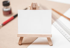 Mini easel with canvas on table with artistic tools. Mini easel with canvas on table with pen, ink, ruler on white table Royalty Free Stock Photos