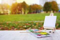 Mini easel, paint and brush on the background of the city park. Draw a landscape in city park. Artist and painting concept. stock photos