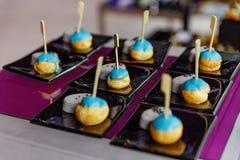 Mini Eclair Glazed med blåttfärgsocker tjänade som med den söta fruktdrycktaroen och svartsesam Royaltyfri Fotografi