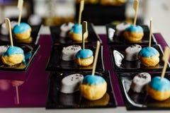 Mini Eclair Glazurujący z Błękitnym koloru cukierem słuzyć z Słodkim przyduszenie taro i Czarnym sezamem Zdjęcie Royalty Free