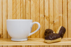 Mini Eclairs with a cup of tea Stock Images