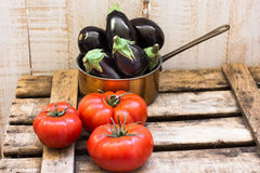 Mini eggplants in copper dipper and ripe raff tomatoes on weathered wood box Royalty Free Stock Photos