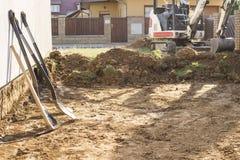 Mini ekskawator na budowie Ekskawator reguluje teren wokoło domu Czerparki głębienia ziemia z łopatami Obraz Stock