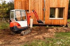 Mini ekskawator na budowie Ekskawator reguluje teren wokoło domu Fotografia Royalty Free