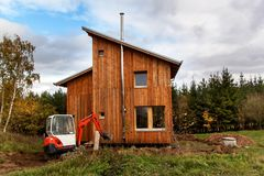 Mini ekskawator na budowie Ekskawator reguluje teren wokoło domu Fotografia Stock