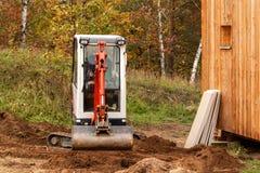 Mini ekskawator na budowie Ekskawator reguluje teren wokoło domu Zdjęcia Royalty Free