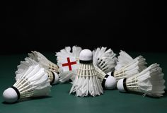 Mini England flag stick on the heap of used shuttlecocks on green floor of Badminton court. With dark black background royalty free stock photos