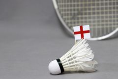 Mini England flag stick on the white shuttlecock on the grey background and out focus badminton racket. Concept of badminton sport stock image