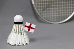 Mini England flag stick on the white shuttlecock on the grey background and out focus badminton racket. Concept of badminton sport royalty free stock images
