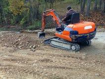 Mini escavatore e lavoratore fotografia stock