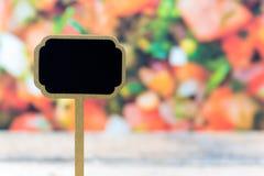Mini etiqueta de madera de la pizarra sobre el fondo vegetal de la ensalada Foto de archivo
