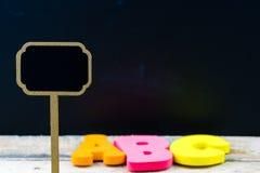 Mini etiqueta de madera de la pizarra sobre fondo de la pizarra Imágenes de archivo libres de regalías