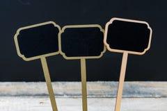 Mini etiquetas de madera de la pizarra sobre fondo de la pizarra Imágenes de archivo libres de regalías
