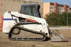 A mini excavator. Bobcat standing at construction site royalty free stock images