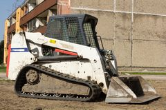 A mini excavator. Bobcat standing at construction site stock photos