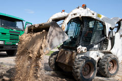 Mini excavator at construction site. Mini Bobcat work on a street reconstruction Royalty Free Stock Photos