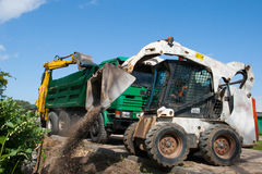 Mini excavator at construction site. Mini Bobcat work on a street reconstruction stock image