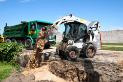 Mini excavator at construction site. Mini Bobcat work on a street reconstruction royalty free stock photography